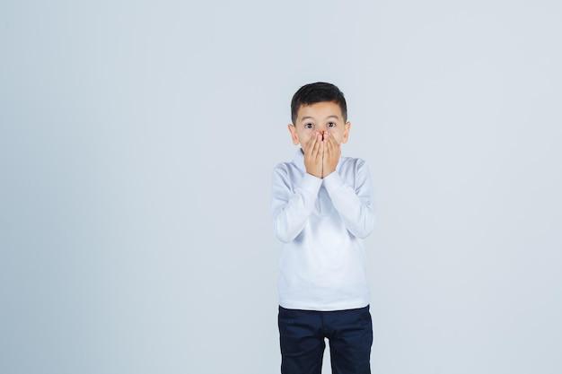 Mały chłopiec trzymając ręce na ustach w białej koszuli, spodniach i patrząc podekscytowany, widok z przodu.