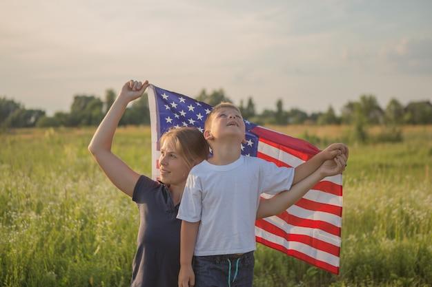Mały chłopiec, trzymając w rękach amerykańską flagę na wietrze na zielonym polu
