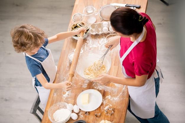 Mały chłopiec, trzymając wałek do ciasta nad drewnianym stołem, stojąc przed matką robiącą ciasto na ciasto