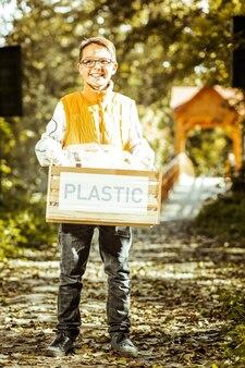 Mały chłopiec trzymający pudełko plastiku do recyklingu na dobry dzień