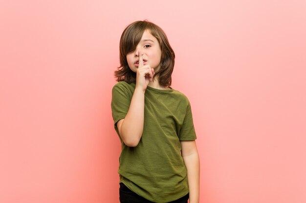 Mały chłopiec trzymający w tajemnicy lub proszący o ciszę.
