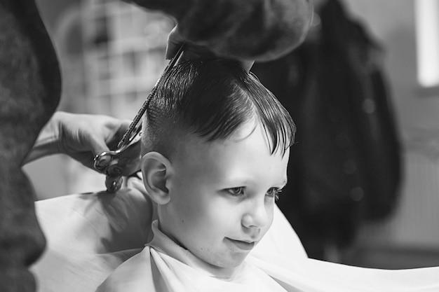 Mały chłopiec u fryzjera. dziecko boi się fryzur. ręce fryzjera co fryzurę do małego chłopca, z bliska. modna fryzura dla chłopców.