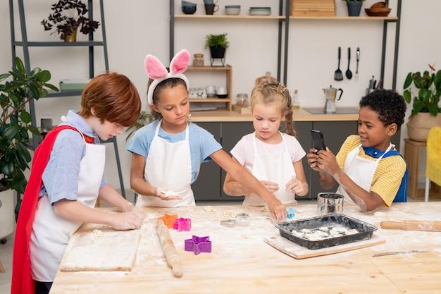 Mały chłopiec ubija mąkę z surowymi jajkami w misce przy kuchennym stole, jednocześnie pomagając mamie z ciastem na ciasteczka