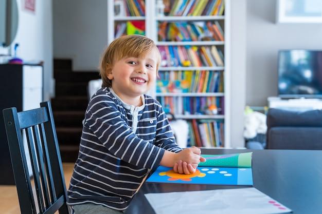 Mały chłopiec ubrany w pasiastą koszulkę siedzi przy stole uczący się w domu podczas blokady koronawirusa maluch śmiejący się podczas lekcji domowej dziecko uczące się zabawy książeczką rozwojową z naklejkami