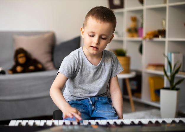 Mały chłopiec uczy się grać na pianinie