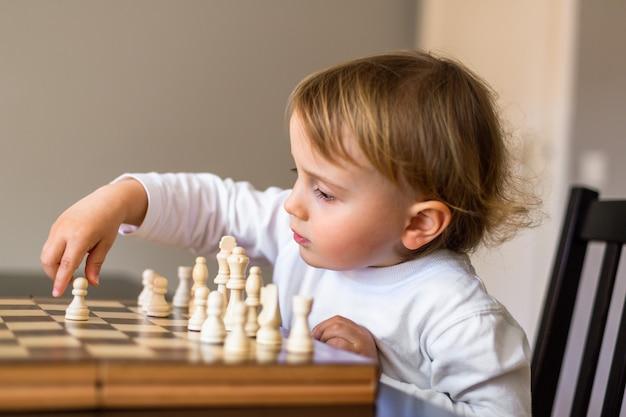 Mały chłopiec uczy się grać w szachy.