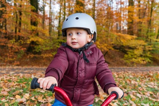 Mały chłopiec uczy się jeździć na rowerze w parku jesienią