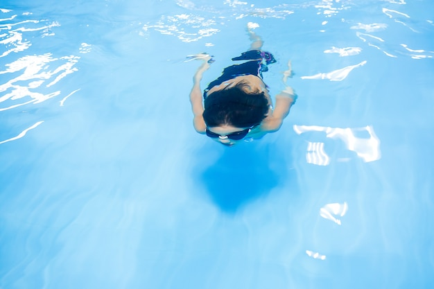 Mały chłopiec uczy się pływać w basenie
