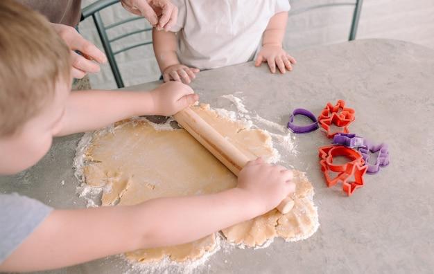 Mały chłopiec uczy się rozwałkować ciasto wałkiem na stole w obecności matki i siostrzyczki. widok z góry