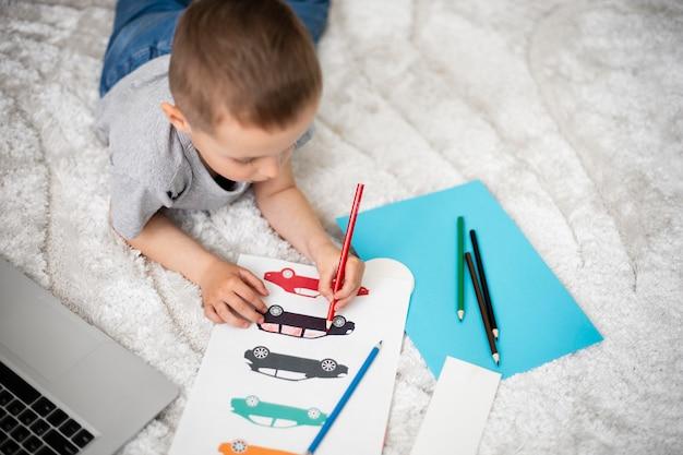Mały chłopiec uczy się rysować