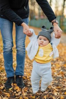 Mały chłopiec uczy się stawiać pierwsze kroki, trzymając się za ręce taty
