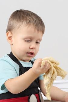 Mały chłopiec ugniata ciasto w dłoniach