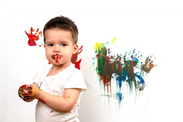 Mały chłopiec umazany farbą stoi na tle białej ściany