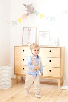 Mały chłopiec umieszcza zabawki w skandynawskim koszu do pokoju dziecięcego. ekologiczny wystrój pokoju dziecięcego. portret chłopca grającego w przedszkolu. pokój dziecięcy i aranżacja wnętrz. chłopiec w domu.