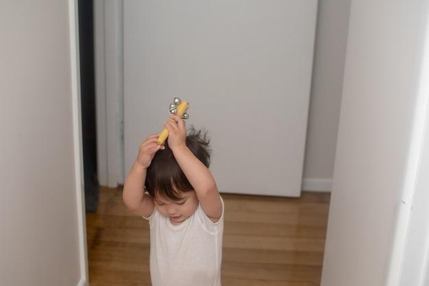 Mały chłopiec unosi dzwonki, instrument muzyczny nad głową