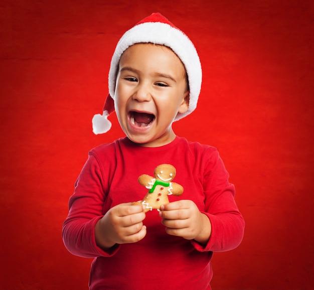 Mały chłopiec uśmiecha przed jedzeniem swoje ciasteczko