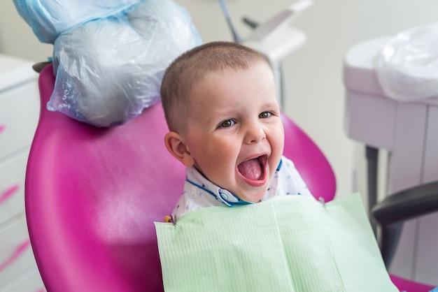 Mały Chłopiec Uśmiecha Się Do Fotela Dentysty Premium Zdjęcia