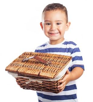Mały chłopiec uśmiecha się i trzyma wiklinowy koszyk