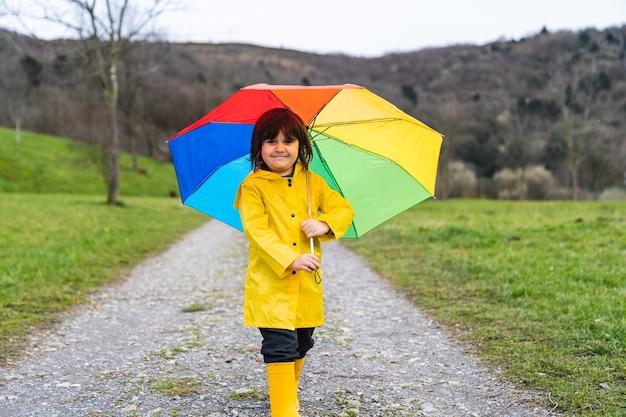 Mały chłopiec uśmiecha się na łące lub leśnej ścieżce w żółtym płaszczu przeciwdeszczowym, żółtych kaloszach i trzyma w dłoni kolorowy tęczowy parasol