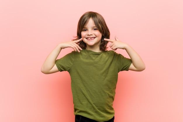 Mały chłopiec uśmiecha się, wskazując palcami na usta.