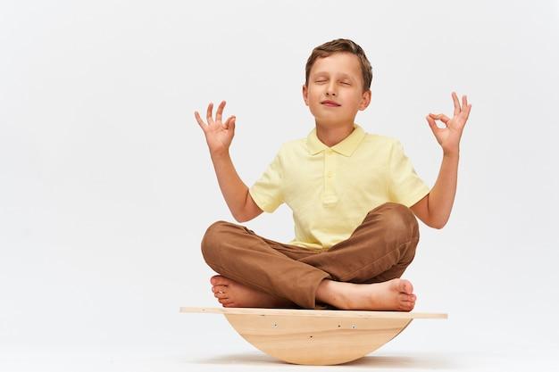 Mały chłopiec utrzymuje równowagę na specjalnym symulatorze do treningu mięśni.