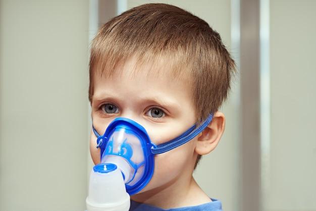 Mały chłopiec używa inhalatora w pomieszczeniu
