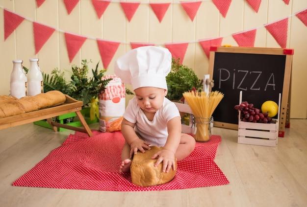 Mały chłopiec w białej czapce szefa kuchni z chlebem siedzi i bawi się w dziecięcej kuchni