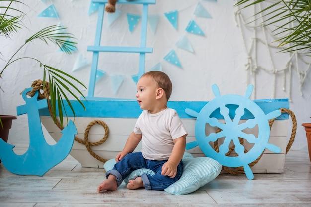 Mały chłopiec w białej koszulce i dżinsach siedzi bokiem do drewnianej łodzi