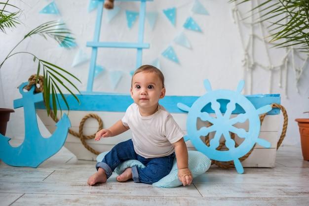 Mały chłopiec w białej koszulce i dżinsach siedzi i odwraca wzrok drewnianą łódką