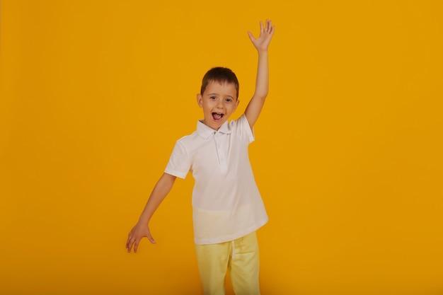 Mały chłopiec w białej koszulce i żółtych spodniach na żółtym tle to emocja