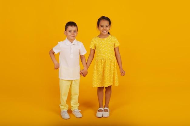 Mały chłopiec w białej koszulce i żółtych spodniach trzyma rękę siostry w żółtej sukience