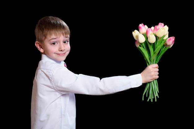 Mały chłopiec w białej koszuli daje bukiet tulipanów.