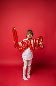 Mały chłopiec w białej koszuli i dżinsach, trzymając czerwony balon w miłości