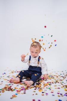 Mały chłopiec w białej koszuli i niebieskich spodniach jest posypany konfetti na białym tle