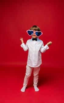 Mały chłopiec w białej koszuli i spodniach ma na sobie duże śmieszne okulary w kształcie serca na czerwono