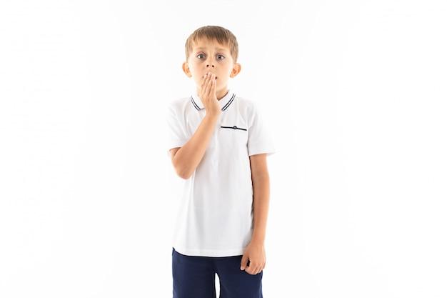 Mały chłopiec w białej koszuli, niebieskich szortach z jasnymi włosami kosztuje, obejmuje firmowymi firmami i strasznie pokona aparat.