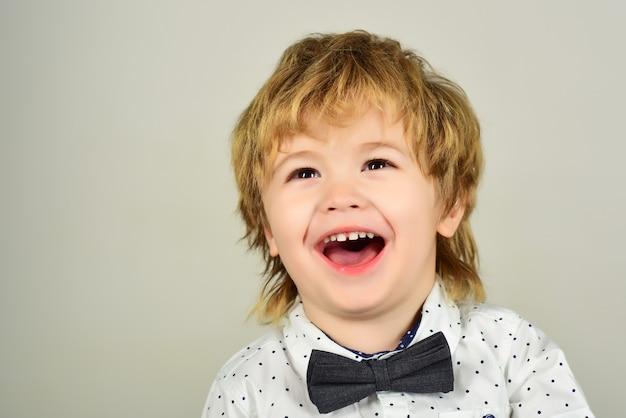 Mały chłopiec w białej koszuli. portret z bliska. ubrania dla dzieci. moda dziecięca. modne małe dziecko w koszuli. szczęśliwy mały chłopiec w białej koszuli z plamami. chłopiec się śmieje. na białym tle na szarym tle.
