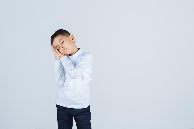 Mały chłopiec w białej koszuli, spodniach, opierając się na dłoniach jako poduszce i patrząc zaspany, widok z przodu.
