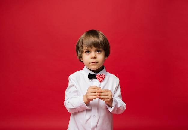 Mały chłopiec w białej koszuli trzyma lizaka na czerwono
