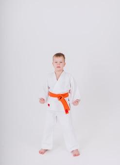 Mały chłopiec w białym kimonie z pomarańczowym paskiem stoi w pozie na białej ścianie z kopią przestrzeni
