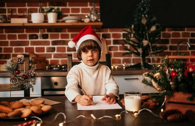 Mały chłopiec w białym swetrze i czerwonej świątecznej czapce siedzi przy kuchennym stole i pisze list noworoczny
