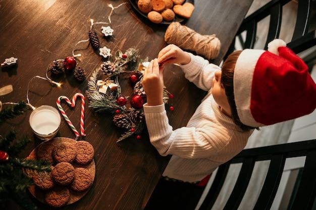 Mały chłopiec w białym swetrze i czerwonym świątecznym kapeluszu siedzi przy kuchennym stole i własnymi rękami robi świąteczny wieniec