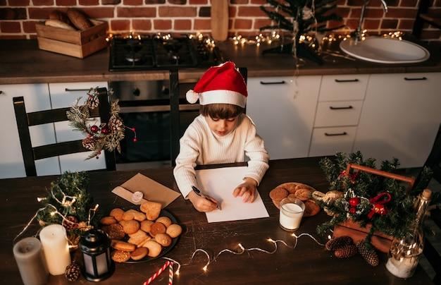 Mały chłopiec w białym swetrze i noworocznej czapce siedzi przy stole i robi listę prezentów na boże narodzenie
