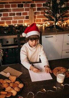 Mały chłopiec w białym swetrze z dzianiny i czerwonej sylwestrowej czapce siedzi w kuchni i pisze wiadomość noworoczną