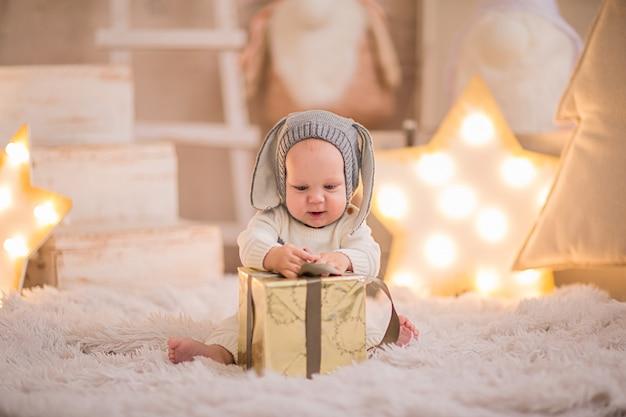 Mały chłopiec w boże narodzenie garnitur jak biały królik bawi się z obecnym pudełku