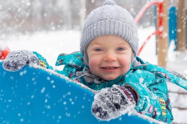 Mały chłopiec w ciepłym kombinezonie bawi się zimą na placu zabaw.