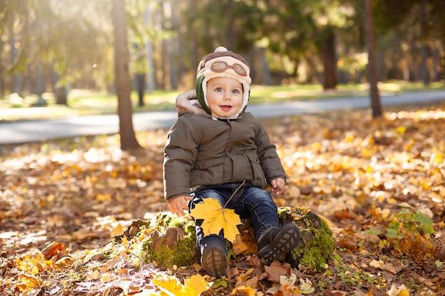 Mały chłopiec w czapce pilota siedzi na pniu, wokół niego żółte i pomarańczowe liście. jesień