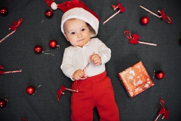 Mały chłopiec w czapce świętego mikołaja leży wśród świątecznych cukierków, kulek i pudełka