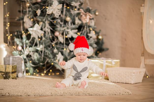 Mały chłopiec w czapce świętego mikołaja, siedząc na podłodze