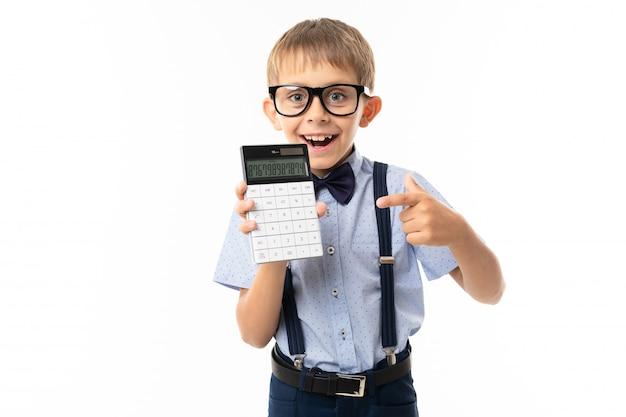 Mały chłopiec w czarnych okularach z przezroczystymi okularami, niebieska koszula, pull-up, niebieskie spodnie pokazuje na kalkulatorze i uśmiecha się